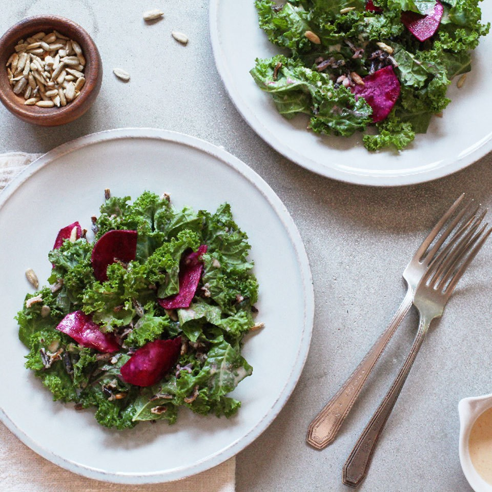 raw kale salad with beets on two white plates with fork and knife