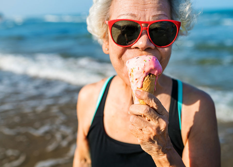 older woman enjoying an ice cream cone on the beach