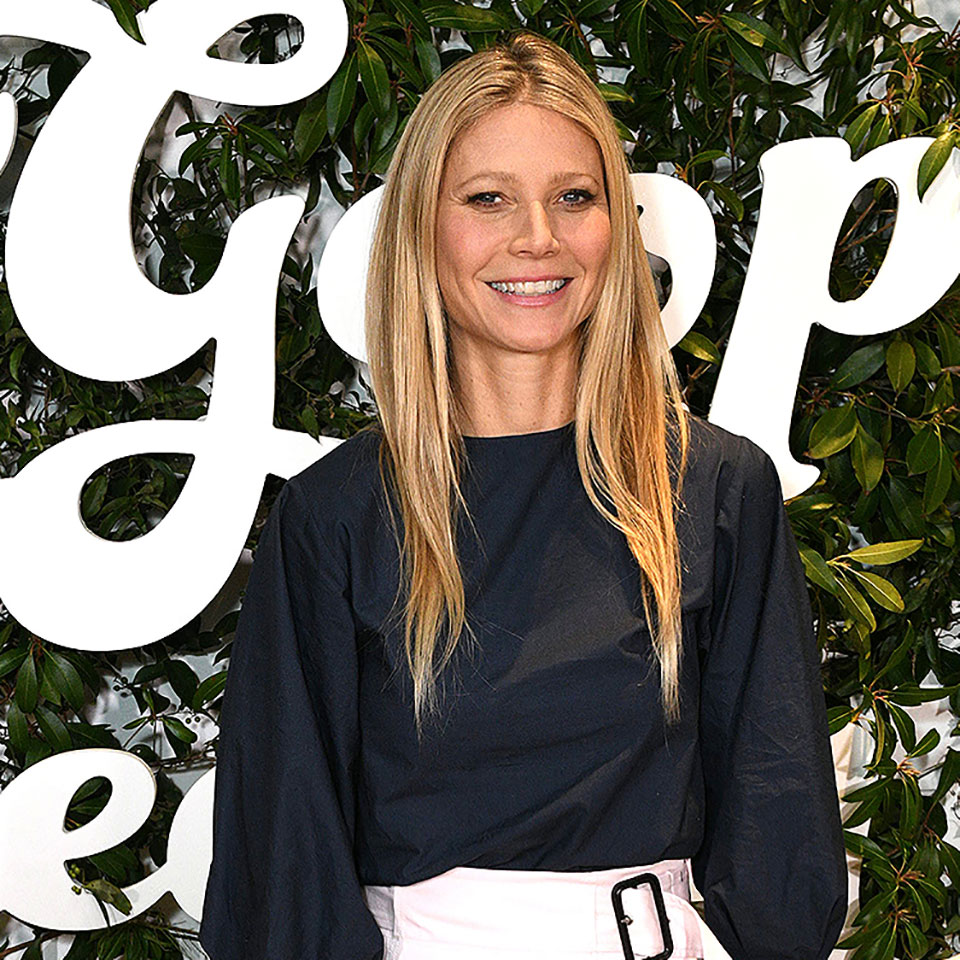 Gwneth Paltrow standing in front of a large Goop logo