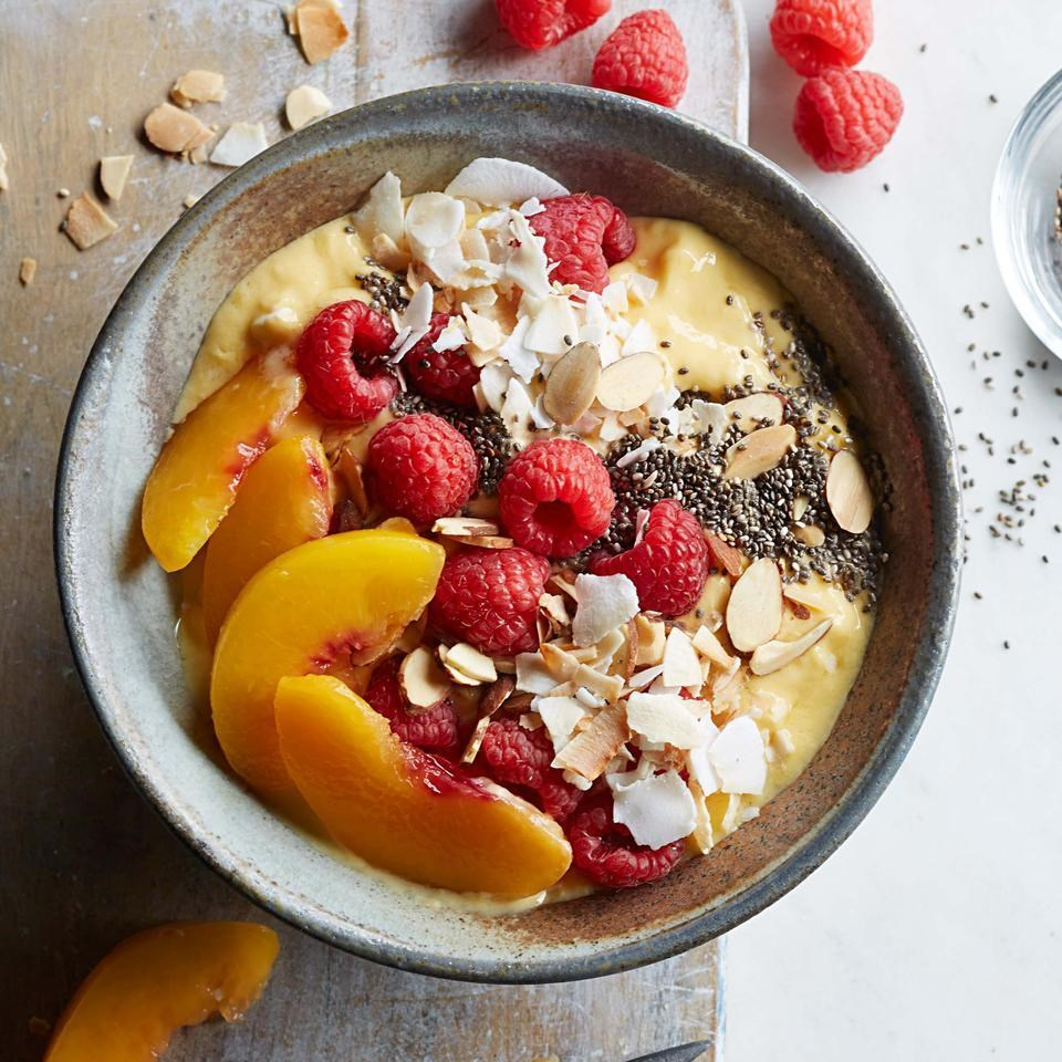 peach smoothie bowl with raspberries and nuts
